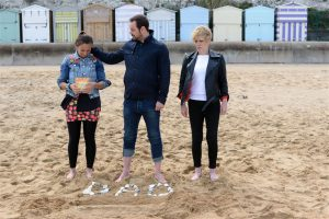 """Eastenders Carter Family in Broadstairs - on the beach with beach huts and pepple memorial to """"Dad"""""""